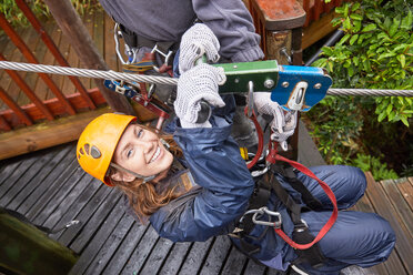 Portrait smiling young woman zip lining - CAIF21431