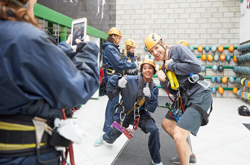 Playful friends in zip line equipment posing - CAIF21434
