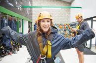 Portrait smiling, confident young woman preparing zip line equipment - CAIF21440