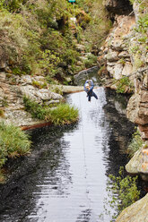 Woman zip lining over stream - CAIF21446