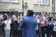 Business people cheering for businessman in courtyard - CAIF21449