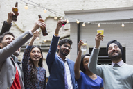 Friends toasting drinks at party on patio - CAIF21467
