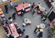 Overhead view friends socializing, drinking and eating at party on patio - CAIF21473