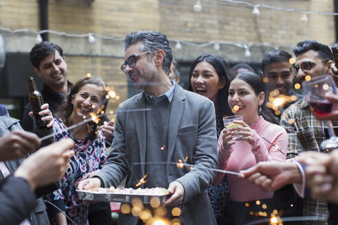Friends with sparklers celebrating with man holding birthday cake - CAIF21479