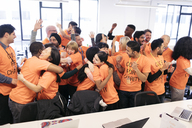 Enthusiastic hackers celebrating, coding for charity at hackathon - CAIF21485