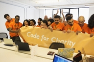 Hackers with banner coding for charity at hackathon - CAIF21488