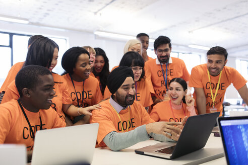 Happy hackers at laptop coding for charity at hackathon - CAIF21506