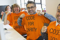 Portrait confident hackers in t-shirts coding for charity at hackathon - CAIF21509