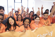 Happy hackers with banner cheering, coding for charity at hackathon - CAIF21518