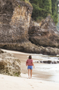 Indonesia, Bali, young woman at the beach, rear view - KNTF01227