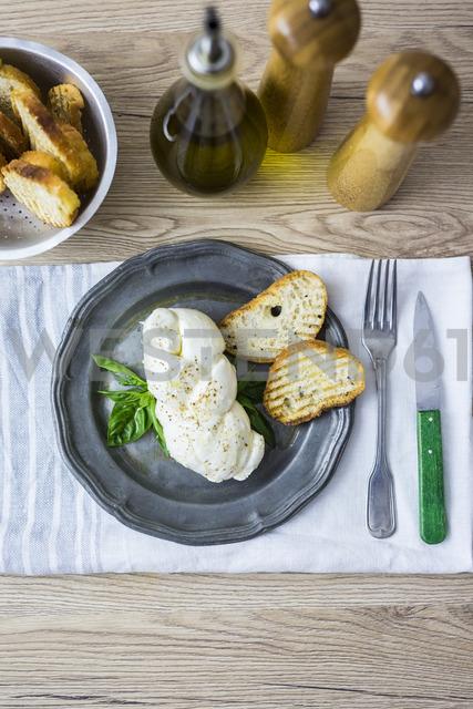Mozzarella braid, basil and bread on plate - GIOF04238 - Giorgio Fochesato/Westend61