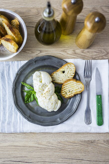 Mozzarella braid, basil and bread on plate - GIOF04238