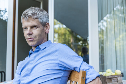Portrait of mature man with grey hair sitting on terrace wearing blue shirt - TCF05643
