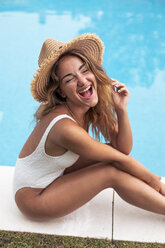 Young girl smiling with straw hat and swimsuit sitting at poolside - ACPF00268