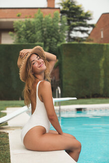 Smiling young woman with straw hat sitting at poolside - ACPF00274
