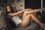 Portrait of young girl wearing a swimsuit sitting on the couch - ACPF00283