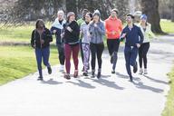 Runner friends running in sunny park - CAIF21584