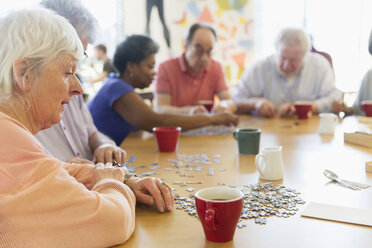 Senior woman assembling jigsaw puzzle with friends at table in community center - CAIF21671