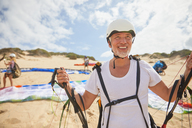 Mature male paraglider on beach with equipment - CAIF21692