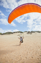 Male paraglider running with parachute on beach - CAIF21704