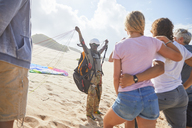 Students watching male paragliding instructor with equipment on sunny beach - CAIF21710