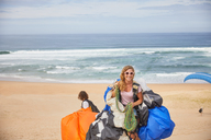 Portrait smiling, confident female paraglider with equipment on sunny ocean beach - CAIF21713