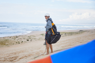 Paraglider with parachute backpack on ocean beach - CAIF21716