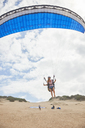 Female paraglider with parachute taking off on beach - CAIF21725