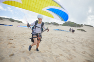 Female paraglider with parachute running, taking off on beach - CAIF21728