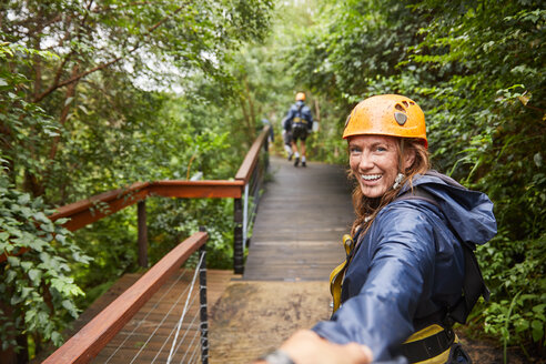 Portrait smiling woman zip lining in woods - CAIF21731