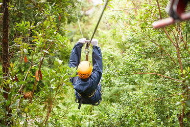 Woman zip lining among trees in woods - CAIF21734