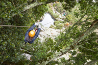 Woman zip lining among trees in woods - CAIF21737