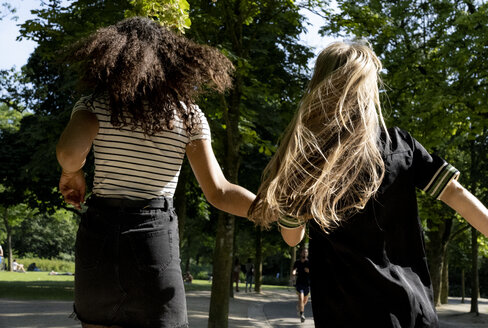 Two girlfriends running in a park, rear view - HHLMF00314