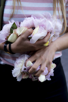 Hands of young woman, holding peonies - HHLMF00326