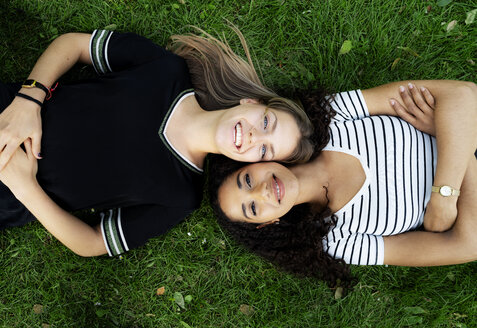 Two girlfriends relaxing in a park, lying on grass - HHLMF00356