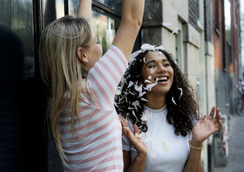 Two happy girlfriends throwing petals - HHLMF00365
