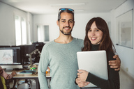 Business couple standing in their office - SUF00540