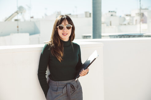 Businesswoman with sunglasses standing on rooftop, holding laptop - SUF00543