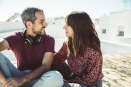 Happy couple sitting on roof, talking, enjoying summer - SUF00549