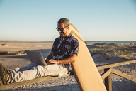 Man sitting at the beach, using laptop, with surfboard leaning on fence - SUF00561