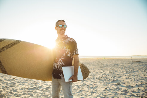 Man at the beach carrying surfboard and laptop - SUF00564