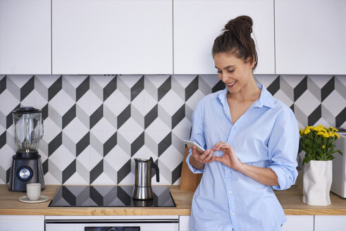 Young woman preparing coffee in the morning, using smartphone - ABIF00901