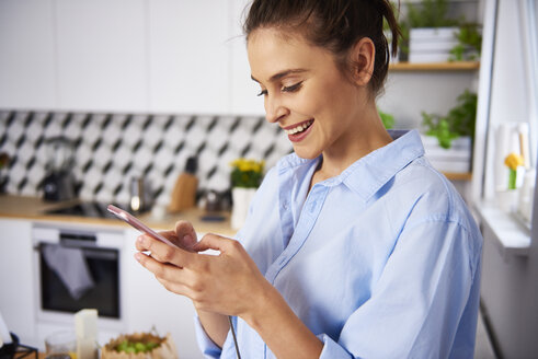 Young woman using smartphone in the kitchen - ABIF00904