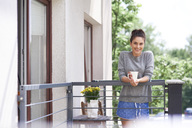 Young woman drinking morning coffee on the balcony - ABIF00919