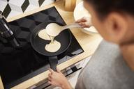 Young woman preparing pancakes - ABIF00925