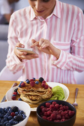 Young woman using smartphone at breakfast - ABIF00934