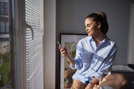 Young woman using smartphone in the morning - ABIF00937