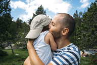 Spain, Father hugging and kissing his little daughter in nature - GEMF02342