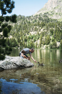 Spain, Father and daughter sitting on a rock at a mountain lake, feeding ducks - GEMF02348