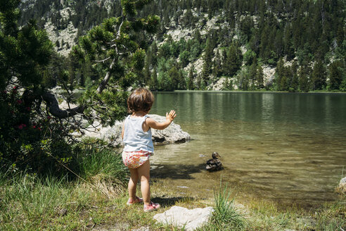 Spain, Little girl standing at mountain lake waving at a duck - GEMF02351